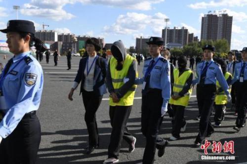 资料图:警方从广州用大巴车将275名电信诈骗犯罪嫌疑人押解回吉林省。张瑶摄