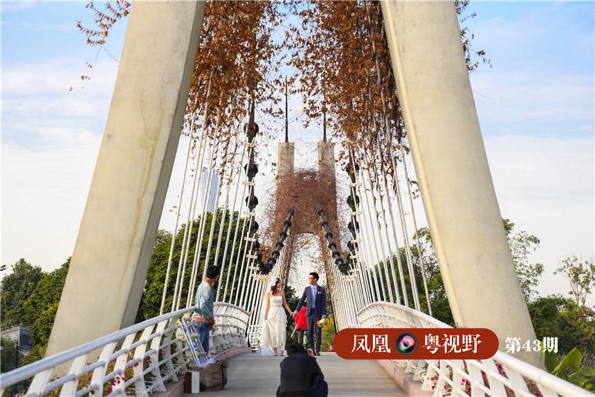 """走至龙潭涌边,视野豁然开朗,眼前一座造型奇特的""""花桥""""连接两岸,引不少游客驻足拍摄。图为:一对新人在花桥上拍摄。"""