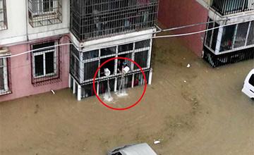 武汉暴雨:住户用水桶从阳台舀水自救
