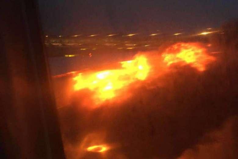 客机引擎起火 乘客只能坐在位子上等着灭火图片