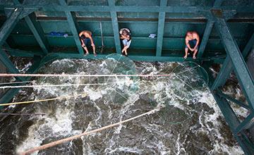 山东:民众不顾危险 泄洪水闸口捞鱼