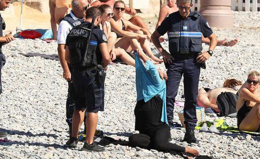 武装警察强制要求穆斯林妇女脱下泳衣一幕