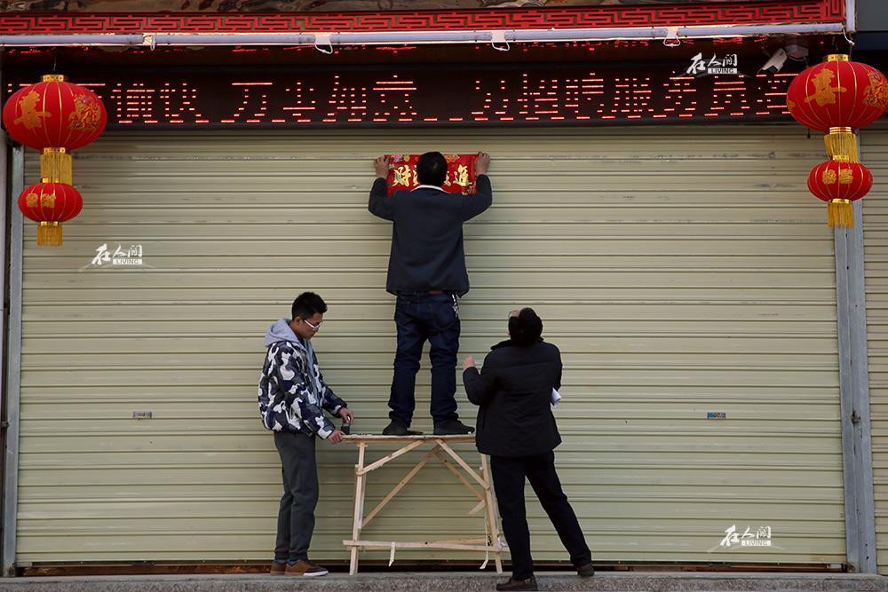 大年三十,街上的店铺大都打烊关张,几个店铺伙计在往卷闸门上贴春联。