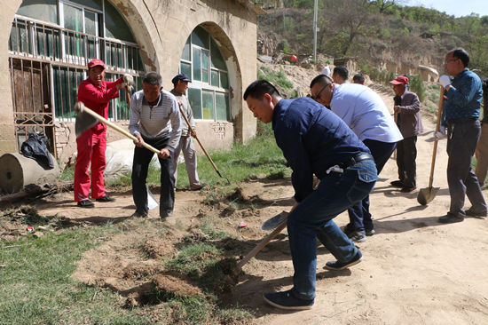 在活动中,宝塔区政协机关党员干部和群众一起对村庄道路两旁杂草