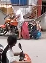 父亲将孩子吊车尾后开动摩托