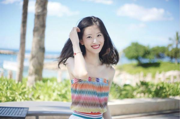 海边度假的她身着条纹彩色抹胸长裙.