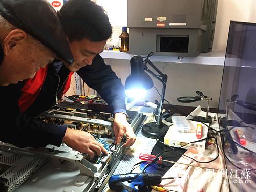 王迺桢老人在志愿者的帮助下修理电视机