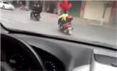 不足10岁小学生骑摩托车载人街道飞驰穿梭