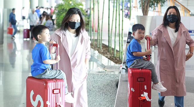 何洁穿粉色风衣素颜现身 让七宝坐行李箱上玩推着走