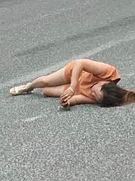 女子在车道上来回翻滚又装晕