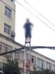 七旬老太街头爬上线缆 吓坏路人