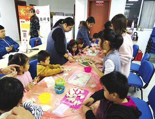 """吴门桥街道南环第三社区开展""""立冬暖心""""传统文化体验活动,家长和孩子们把饺子包成了自己喜欢的形状。(肖萍/摄)"""