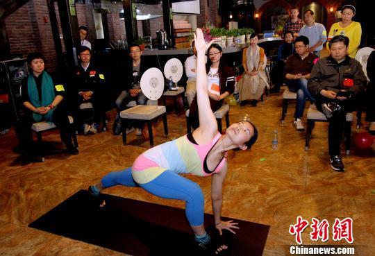 健康导师李涛(前)为企业家示范瑜伽动作。 张道正 摄