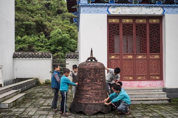 2016年4月24日,江西兴国市三僚村,村里的小孩在玩一个挂钟。钟上刻有堪舆的口诀。本文图片 澎湃新闻记者 陈荣辉