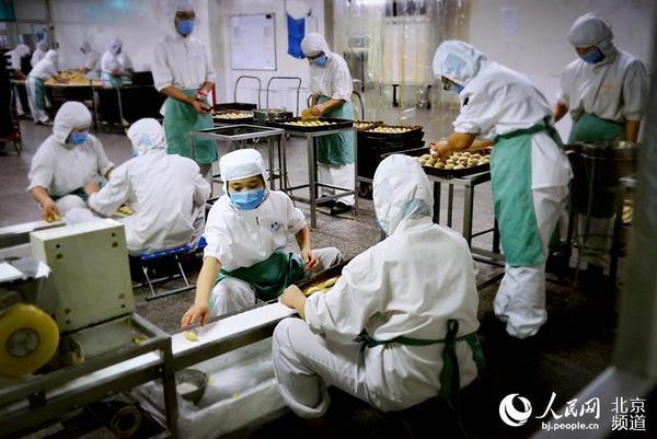 干净整洁的生产车间内,工人们井然有序地进行糕点加工作制.