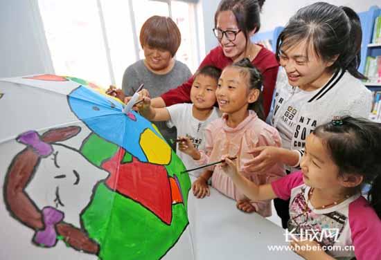 社区工作人员和小朋友共同彩绘雨伞.