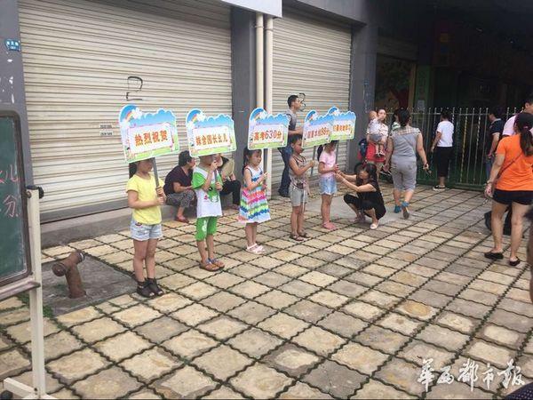"""5位小朋友站成一排,各自举着一块牌子,连起来一句话为:""""热烈祝贺姝含园长幺儿高考630分,超重本线98分,我们要向她学习。"""" 原标题:幼儿园小朋友举牌祝贺园长幺儿高考630分 华西都市报讯(客户端记者田雪皎)6月23日下午4时30分许,四川资阳城区一幼儿园门口,5位小朋友站成一排,各自举着一块牌子,连起来一句话为:""""热烈祝贺姝含园长幺儿高考630分,超重本线98分,我们要向她学习。""""随后,幼儿园园长承认,确系幼儿园安排所为,但是是由家长提出来的,目的是给幼"""