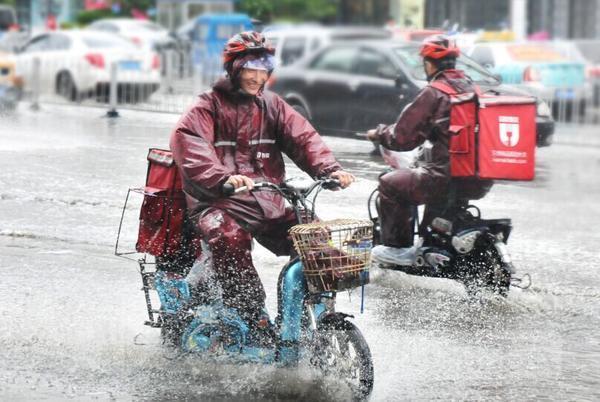 急雨绊住外卖骑士步伐