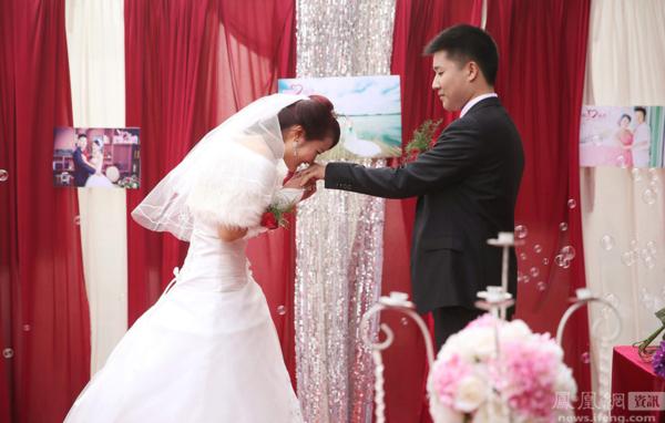 资料图片:2015年2月16日,安徽省滁州市的一场婚礼上,新娘为新郎戴上婚戒,并献上一吻。