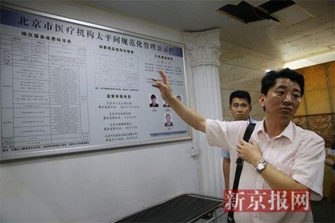执法人员查看东方医院太平间悬挂的收费公示栏.新京报记者尹亚飞摄