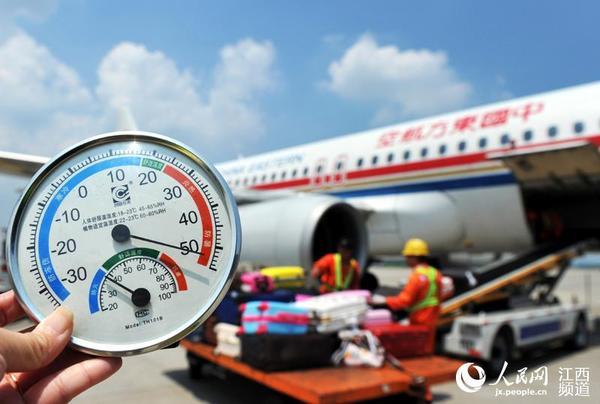 南昌昌北机场停机坪的温度超过50℃,飞机落地,地勤人员忙着装卸行李.