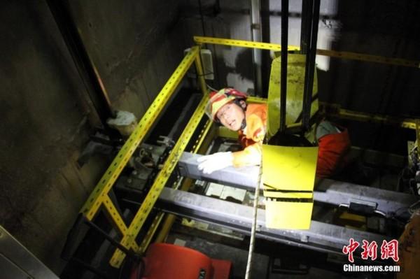 8月22日上午10时20分许,湖北巴东县一酒店主楼电梯突然停止运行,且电梯门无法正常打开,导致电梯内有14名人员被困。当地消防部门接到报警后,立即出动1辆抢险救援车、7名官兵赶赴现场营救。救援时,消防官兵来到电梯轿厢上方,利用金属切割机切开一个小口,使用送风机对电梯轿厢内进行送风,保证空气流通,并送上水和葡萄糖等物资。与此同时,消防官兵利用电锤、铁锹等工具,对电梯轿厢正对的墙面进行破拆开孔。经过一个多小时的紧张作业,消防官兵成功将墙面破开,并利用拉梯先后将14名被困人员营救出来,转移至安全地带。图为消防