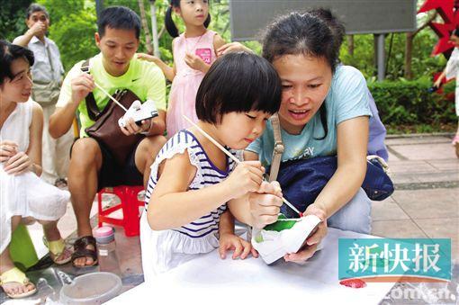 ■一个小女孩在家长的协助下在鞋子上涂鸦。    新快报记者 毕志毅/摄
