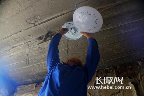 电工师傅帮助贫困户安装遥控智能LED照明灯。
