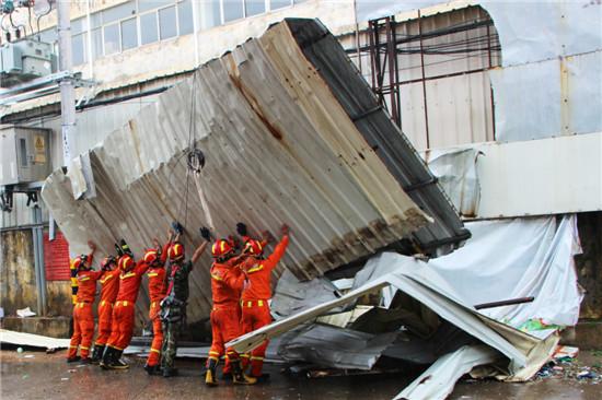 消防官兵处理倒塌的铁皮,保持道路通畅