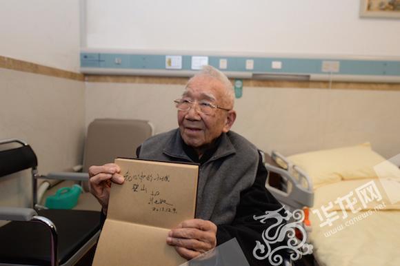 """庄奴展示自己所写的""""我心中的小城,璧山""""。通讯员 舒畅 摄 华龙网发"""