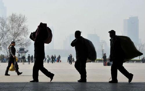 几名外来务工人员扛着行李。新华社发