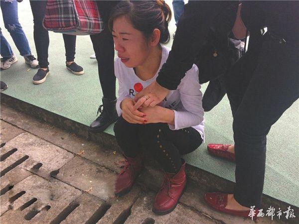 郑�_死者妈妈郑女士伤心坐在案发地旁.