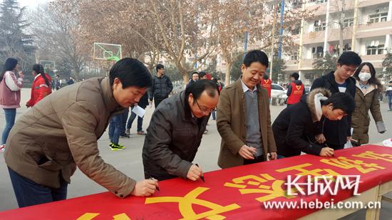学校领导带头签名。王雅茹 摄