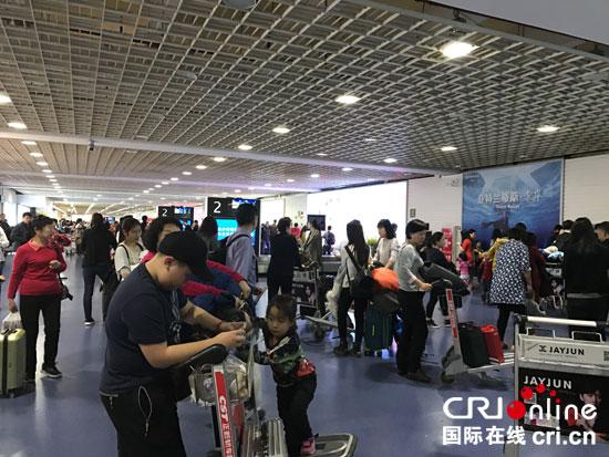 从北京飞抵三亚的某航班行李转盘旁,好多以家庭为单位的旅客在等待