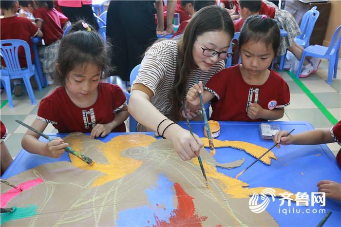 纸箱制作出龙头,与小朋友们一起进行绘画,又在一起制作出了龙舟的身体