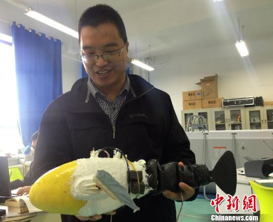 图为兰州交通大学机器人创新创业基地负责人李宗刚展示机器鱼。 徐雪摄