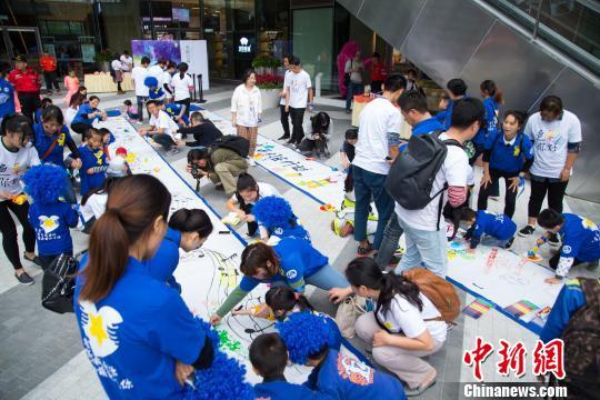福州麦顶小学的孩子们与自闭症儿童一起绘制百米画卷。 李南轩摄