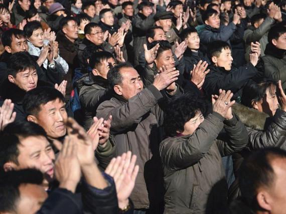 11月29日,朝鲜平壤街头,民众在听到巨型显示屏播报的成功试射弹道导弹消息后鼓掌祝贺。(新华/法新)