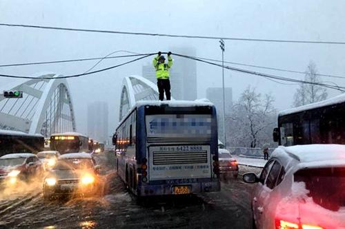 合肥蒙城路桥大雪压电缆挂住公交车民警爬到车顶托举20多分钟