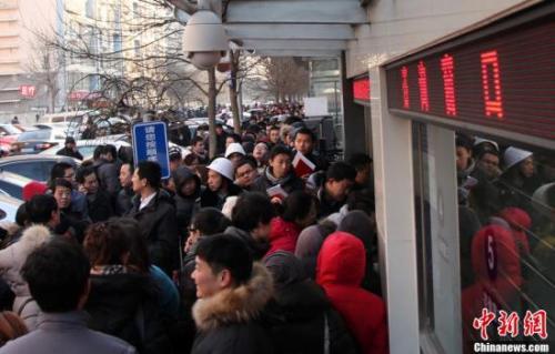 资料图:北京朝阳区房屋登记发证大厅外排队领号准备办理过户手续的市民。 韩海丹摄