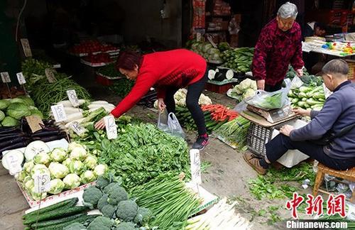 1月10日,中国国家统计局公布的数据显示,2017年12月份中国CPI同比上涨1.8%。从全年数据来看,2017年全年CPI比上年上涨1.6%。图为成都某市场内蔬菜标注的价格,一些民众正在挑选。(资料图)中新社记者刘忠俊摄