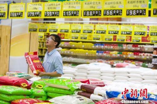 民众在超市查看大米售价。 张云摄