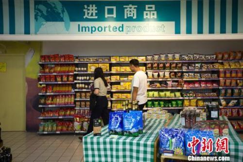 民众在超市进口商品货架前选购商品。 张云摄