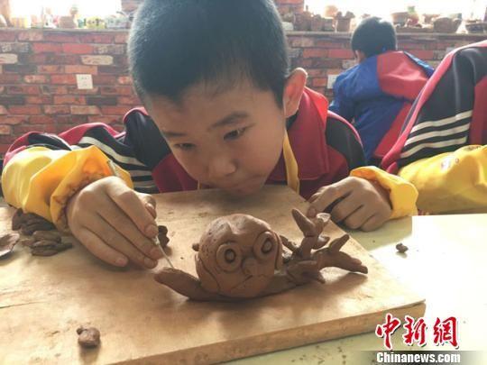 """实验三小陶艺课上,五年级学生王博文在自己作品上用木刀再加工,""""树干""""上显现出一条条纹路。 张婧摄"""