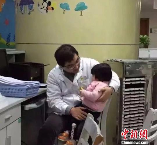 图为男孩父亲抱着儿童患者为其讲故事。 绍兴市人民医院供图摄
