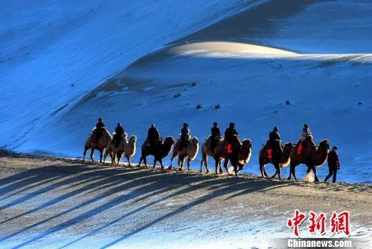 """图为游客骑骆驼穿行于""""沙雪""""间。(资料图) 张晓亮摄"""