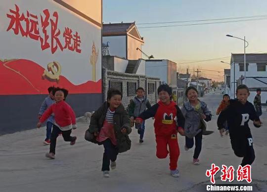 图为兰考县仪封乡代庄村街头,一群放学的孩子在规划整齐的街头嬉戏。兰考官方供图