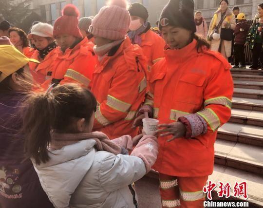 图为小志愿者为环卫工人送去腊八粥。 姜尧摄