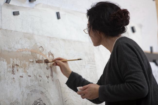 关晋文正在认真地修稿,大约三平米大小的壁画,需要两年才能完成现状临摹。