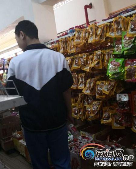 在海口琼山华侨中学内的超市,一名学生在选购食品。